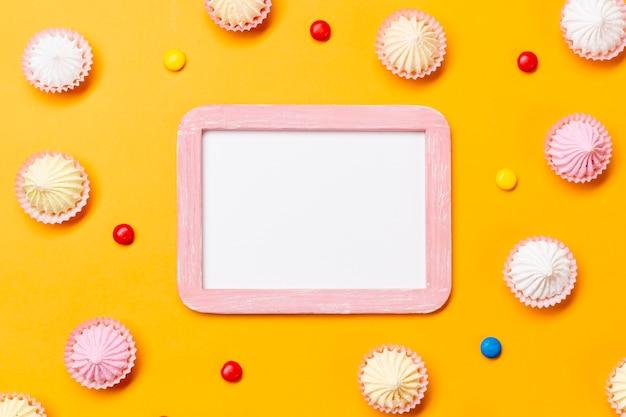 Marco blanco en blanco rodeado de coloridas gemas y aalaw sobre fondo amarillo Foto gratis