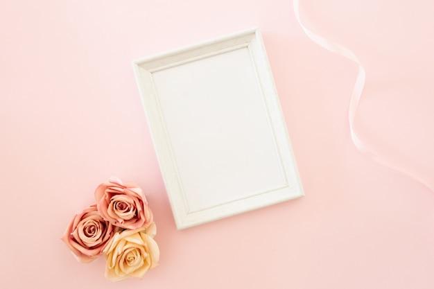 Marco de boda blanco con rosas sobre un fondo rosa Foto gratis