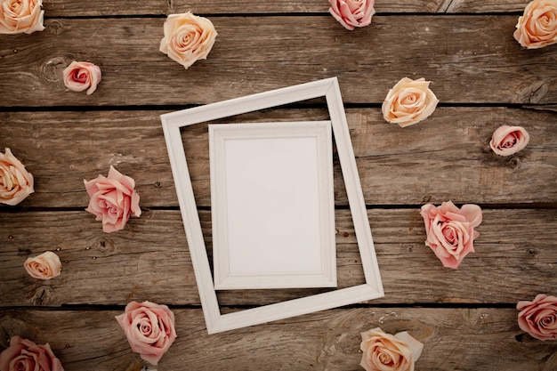 Marco de boda con rosas rosadas sobre fondo de madera marrón. Foto gratis