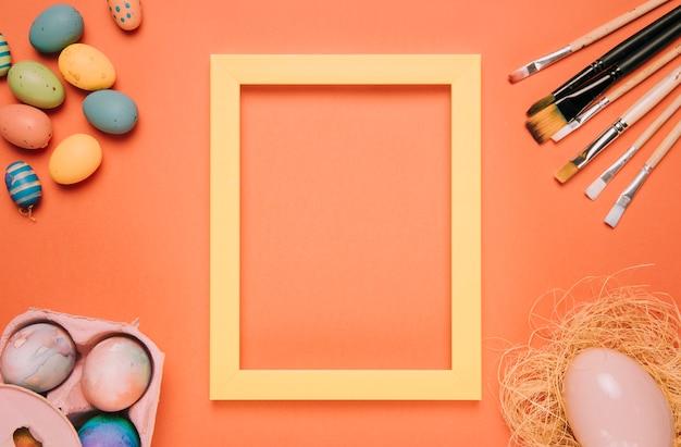 Marco de borde amarillo rodeado de huevos de pascua; nido y pinceles sobre un fondo naranja. Foto gratis