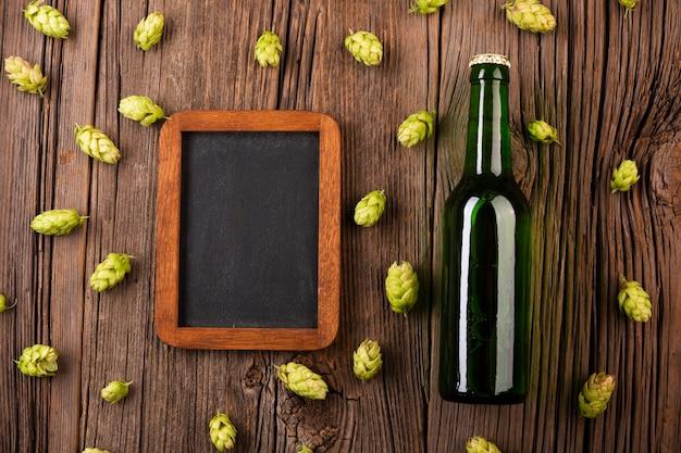 Marco y botella de cerveza sobre fondo de madera Foto gratis