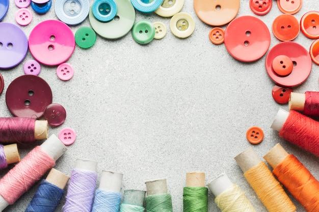 Marco de botones de colores y rollos de hilo con espacio de copia Foto gratis