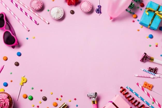 Marco circular en blanco hecho con artículos de fiesta de cumpleaños sobre fondo rosa Foto gratis