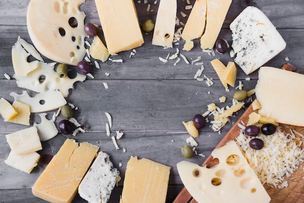 Marco circular hecho con diferentes tipos de queso y aceitunas en mesa de madera Foto gratis