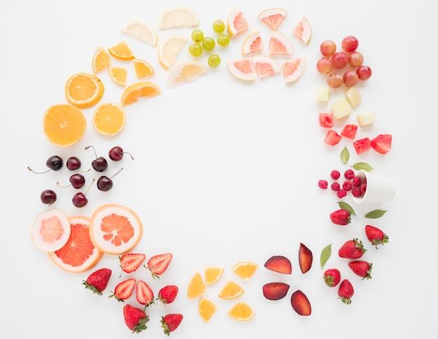 Marco circular hecho con muchas rodajas de frutas sobre fondo blanco Foto gratis