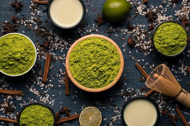 Marco de cuencos con polvo verde y tazas de té. Foto gratis