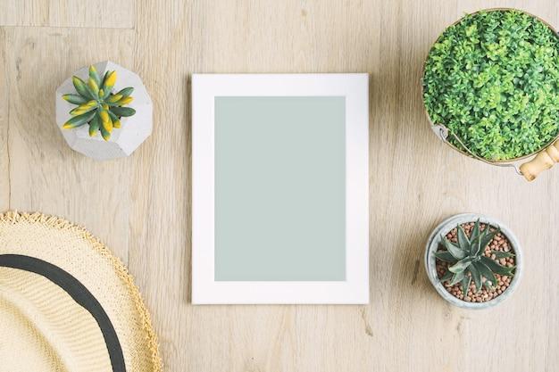 Marco de fotos en blanco colocado en un piso de madera adornado con ...