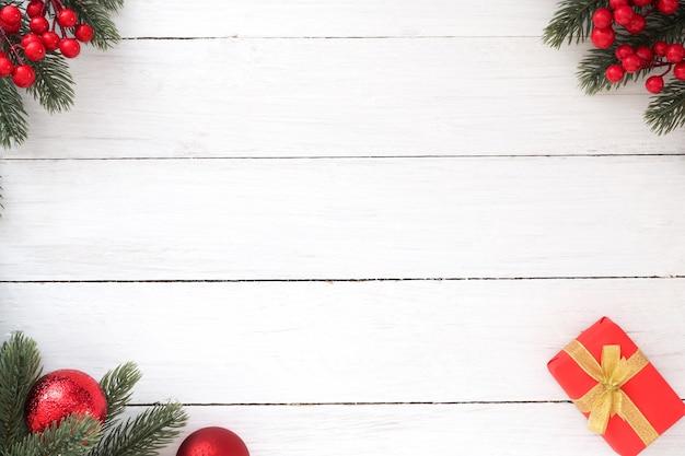 Marco de navidad hecho de hojas de abeto, caja de regalo roja, bayas ...