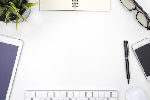 Marco con equipo de oficina en escritorio blanco Foto gratis