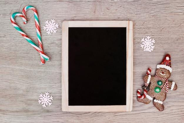 Marco de fotos entre bastones de caramelo colocados en forma de corazón y galleta muñeco de nieve Foto gratis