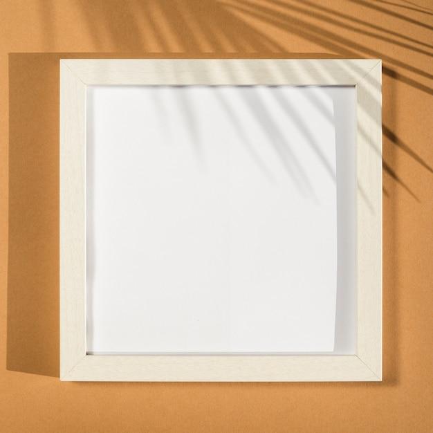 Marco de fotos blanco sobre un fondo beige con una sombra de hoja de palma Foto gratis
