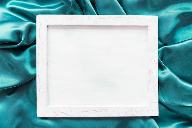 Marco de fotos en blanco sobre tela satinada turquesa. Foto gratis