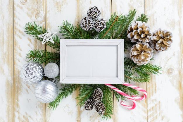 Marco de fotos entre la decoración de navidad, con bolas blancas y piñas en una mesa de madera blanca. vista superior, marco para copiar espacio Foto Premium