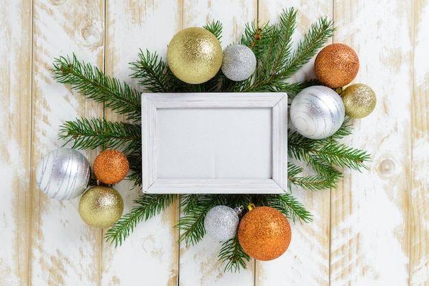 Marco de fotos entre la decoración de navidad, con bolas de color naranja y blanco sobre una mesa de madera blanca. vista superior, marco para copiar espacio. Foto Premium