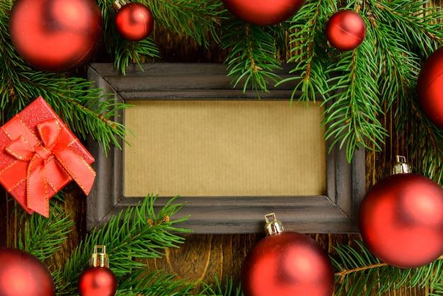 Marco de fotos entre la decoración de navidad, con bolas rojas y caja de regalo sobre una mesa de madera marrón. vista superior, marco para copiar espacio. Foto Premium