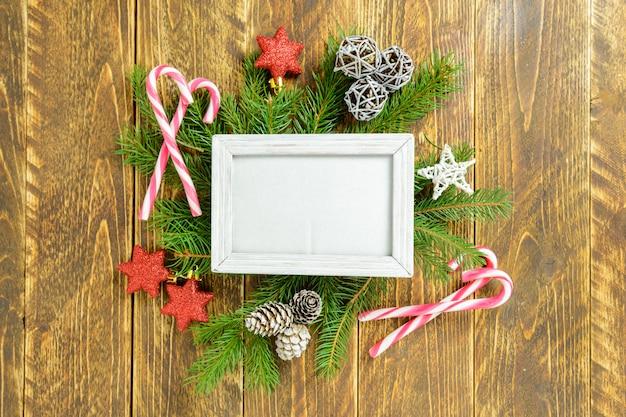 Marco de fotos entre la decoración de navidad, con estrellas y bastón de caramelo sobre una mesa de madera marrón. vista superior, marco para copiar espacio. Foto Premium
