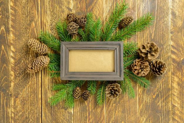 Marco de fotos entre la decoración de navidad, con piñas en una mesa de madera marrón. vista superior, marco para copiar espacio. Foto Premium