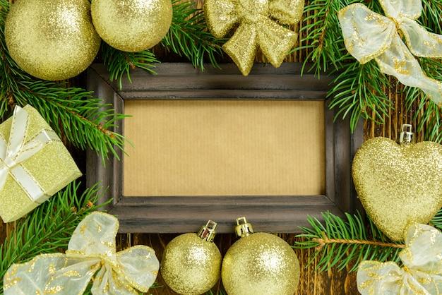 Marco de fotos entre decoración navideña, con bolas de color dorado y cintas sobre una mesa de madera marrón. vista superior, marco para copiar espacio. Foto Premium