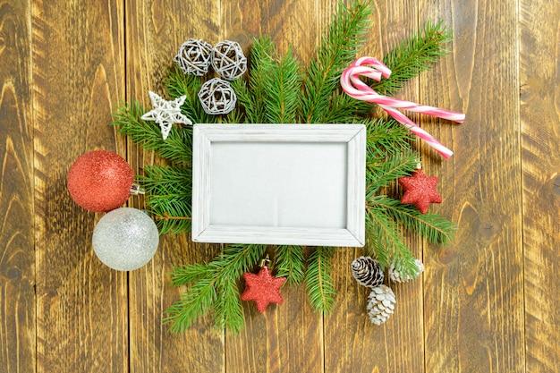 Marco de fotos entre decoración navideña, con bolas de colores y bastón de caramelo sobre una mesa de madera marrón. vista superior, marco para copiar espacio. Foto Premium