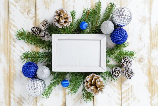 Marco de fotos entre decoración navideña, con bolas de colores y conos de pino sobre una mesa de madera blanca. vista superior, marco para copiar espacio. Foto Premium