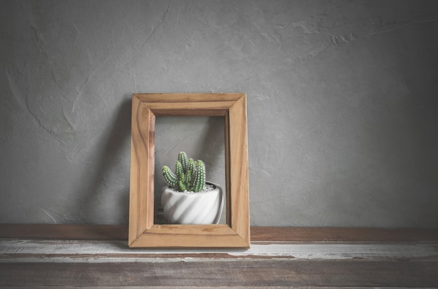 Marco de fotos con flores de cactus en la mesa de madera concepto de conservación de la naturaleza. Foto Premium