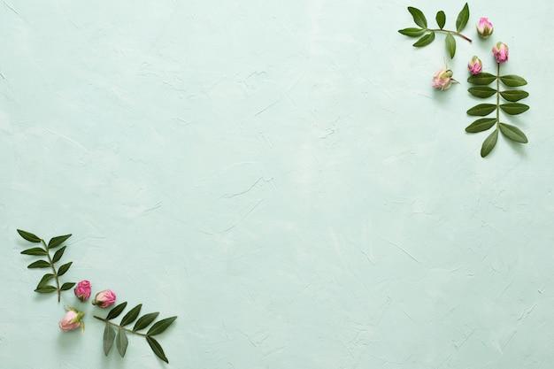 Marco hecho marco flores color de rosa y hojas sobre fondo verde Foto gratis