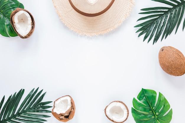 Marco de hojas de palmera, cocos y sombrero de paja. Foto gratis