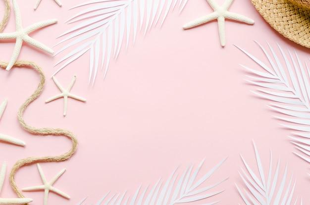 Marco de hojas de palmera, estrellas de mar y sombrero de paja. Foto gratis