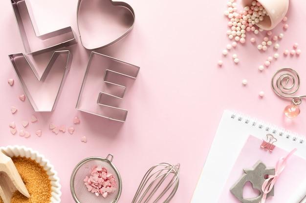 Marco de ingredientes alimenticios para hornear en un pastel suavemente rosa. concepto de horneado Foto Premium