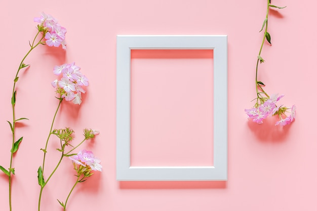 Marco de madera blanca y flores sobre fondo rosa con espacio de copia. Foto Premium