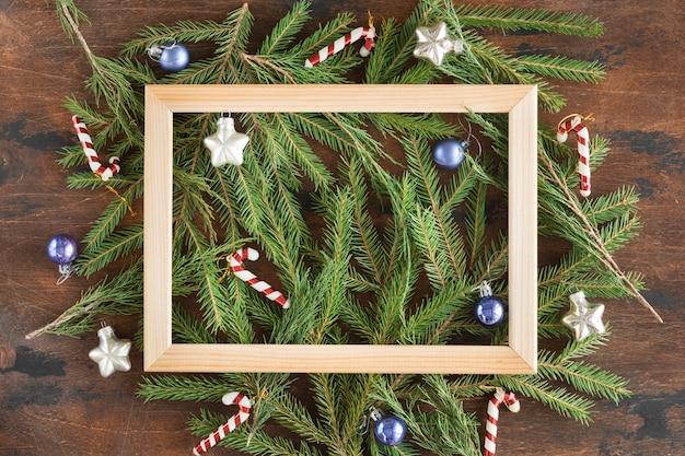 Marco de madera hecho de ramas de abeto y adornos navideños en madera oscura Foto Premium