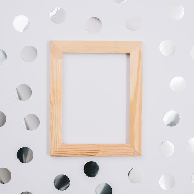 Marco de madera con lentejuelas en mesa Foto gratis