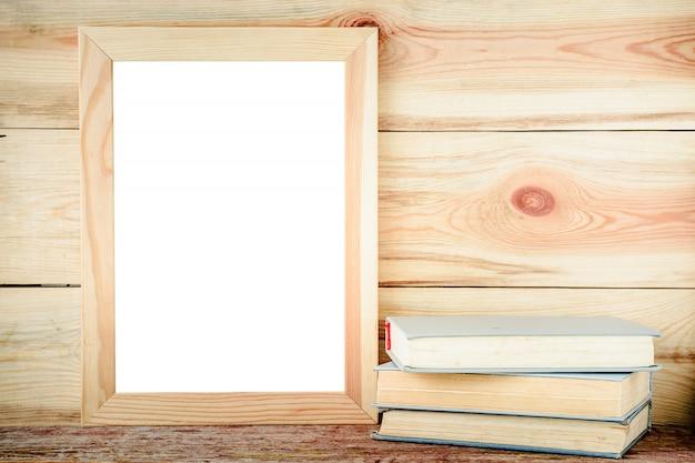 Marco de madera maqueta y libros antiguos sobre un fondo de madera Foto Premium