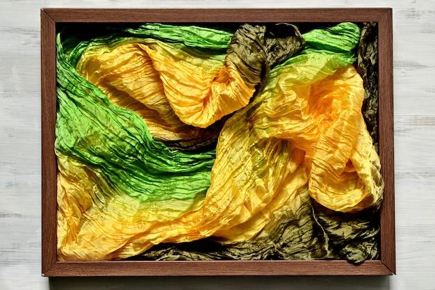 Marco de madera con tela de seda de colores amarillo, verde