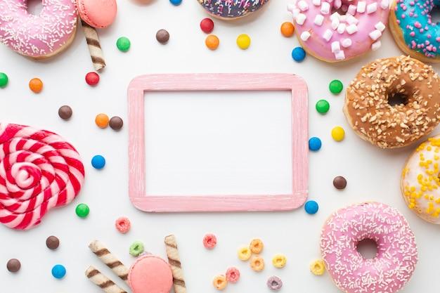 Marco de maqueta rodeado de dulces Foto gratis