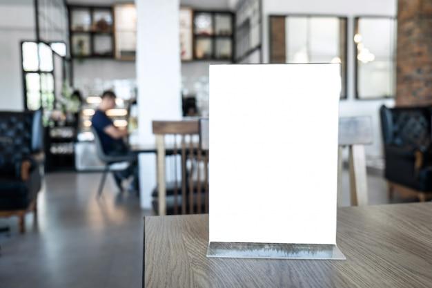 Marco de menú de maqueta de pantalla en blanco de pie sobre la mesa de madera en el fondo Foto Premium