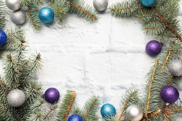 Marco de navidad hecho de abeto, decoraciones para árboles de navidad en plata y azul sobre un fondo de ladrillo claro. copia espacio endecha plana. Foto Premium