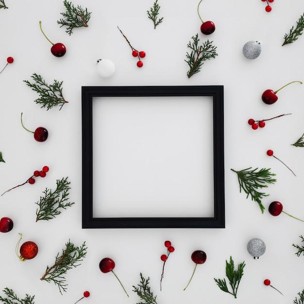 Marco negro con patrones hechos con hojas de pino y bolas decorativas de navidad. Foto gratis