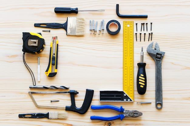 Marco o composición de las herramientas de construcción para la renovación de una casa o apartamento, sobre una mesa de madera. el lugar de trabajo del capataz. el tema del hogar y la reparación profesional, construcción. Foto Premium