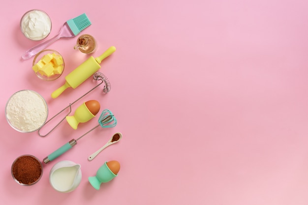 Marco de la panadería de alimentos, concepto de cocina. ingredientes en la mesa de la cocina. mantequilla, azúcar, harina, huevos, aceite, cuchara, rodillo, cepillo, batidor sobre fondo rosa. Foto Premium