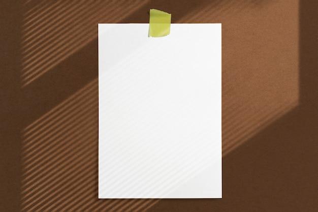 Marco de papel en blanco de tamaño 10 x 15 pegado con cinta adhesiva a la pared con textura marrón con suaves sombras de ventana de adobe Foto gratis