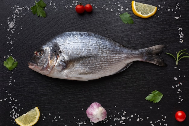 Marco plano de condimentos con pescado en el centro Foto gratis
