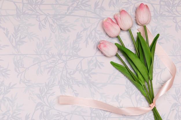 Marco plano laico con tulipanes sobre fondo floral Foto gratis