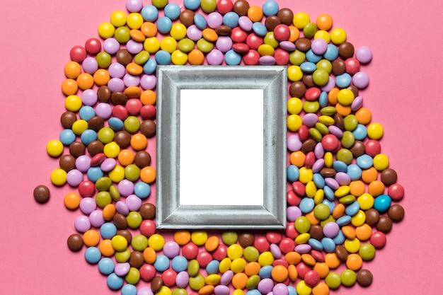 Un marco de plata vacío sobre los caramelos coloridos de la gema en el fondo rosado Foto gratis