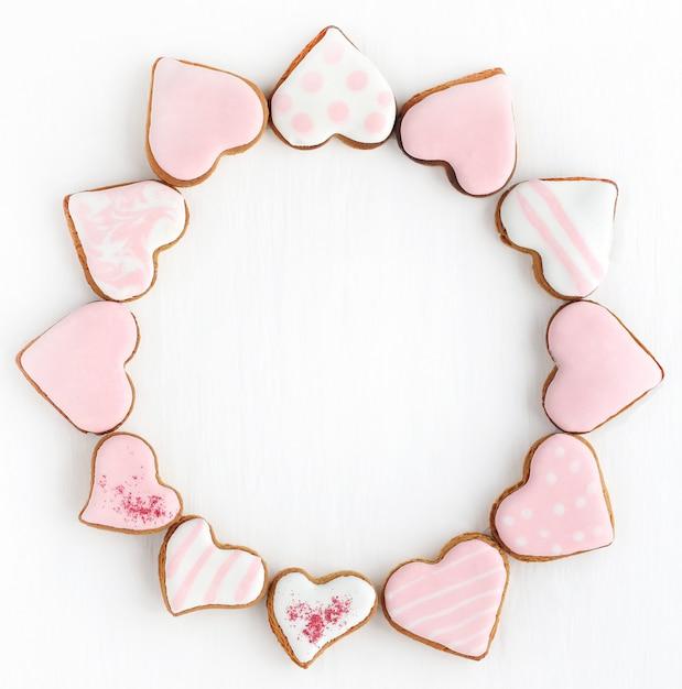 Marco redondo de pan de jengibre en forma de corazón de diferentes tamaños en esmalte blanco y rosa sobre un fondo blanco. espacio para texto. Foto Premium