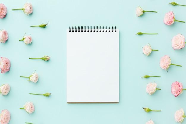 Marco de rosas rosadas con bloc de notas vacío Foto gratis