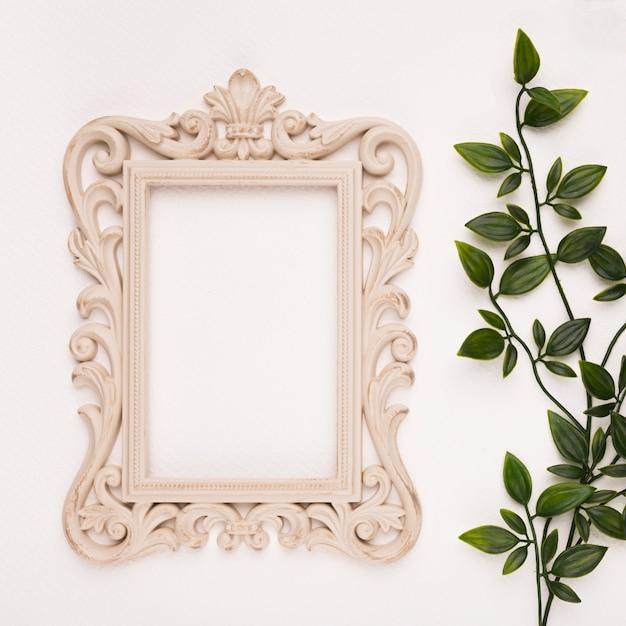 Marco de talla de madera cerca de las hojas artificiales sobre fondo blanco. Foto gratis