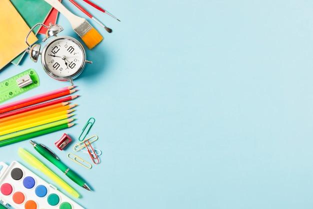 Marco de útiles escolares sobre fondo azul claro Foto gratis