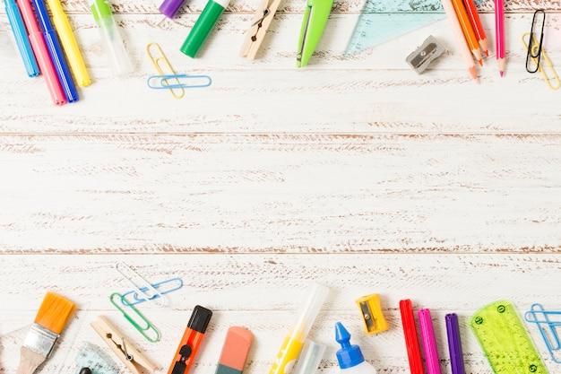 Marco de útiles escolares sobre fondo de madera Foto gratis
