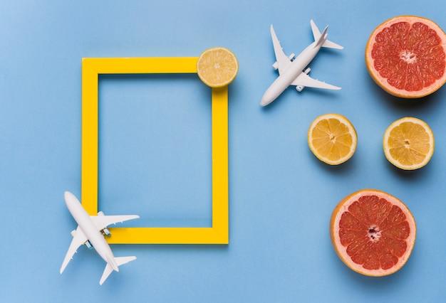 Marco vacío, aviones de juguete y fruta. Foto gratis